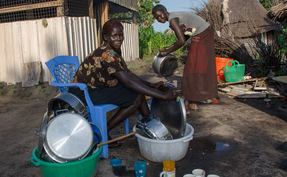 Tabitha and Rebecca, ASAH cooks, scrub the dishes outside our temporary kitchen.